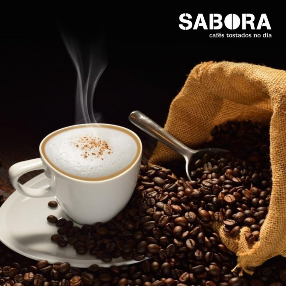 Café al lado de saco con granos de café