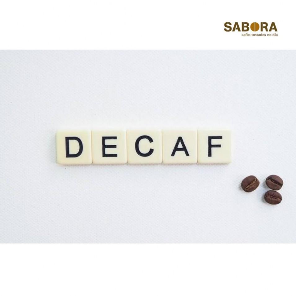 A palabra decaf con tres grans de café ecolóxico