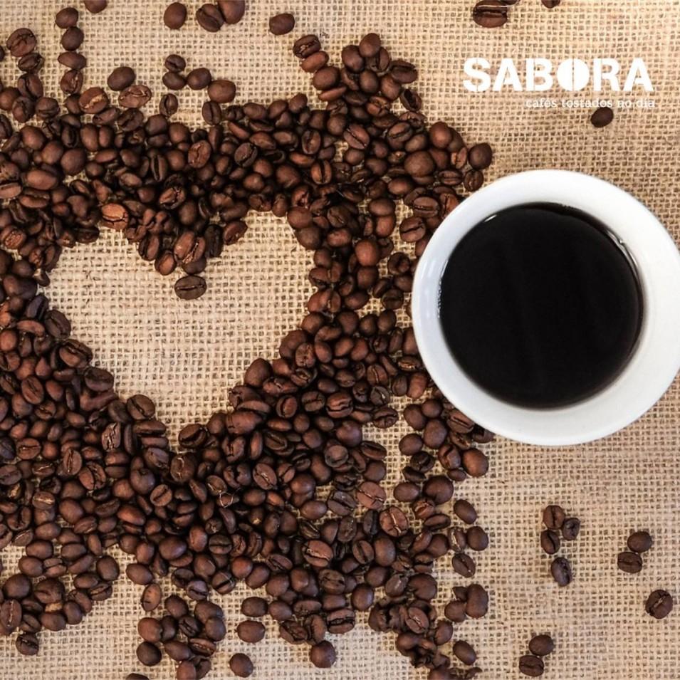 Cunca de café e corazón de grans de café sobre unha mesa.