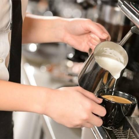 Barista facendo café con leite en cafeteira expreso