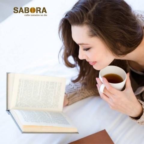 Mujer tomando café en casa mientras lee un libro